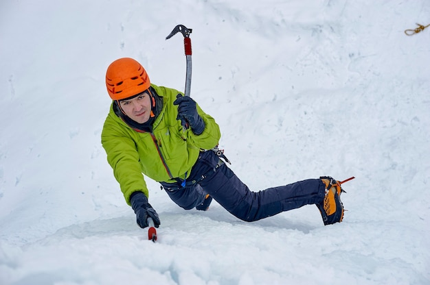 Alpinist man with ice tools axe in orange helmet climbing a large wall of ice. outdoor sports portrait.