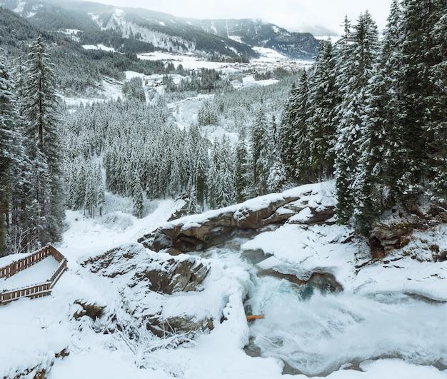 Красивый горный водопад в альпах, кримль, австрия, зимний вид на тироль со смотровой площадкой.
