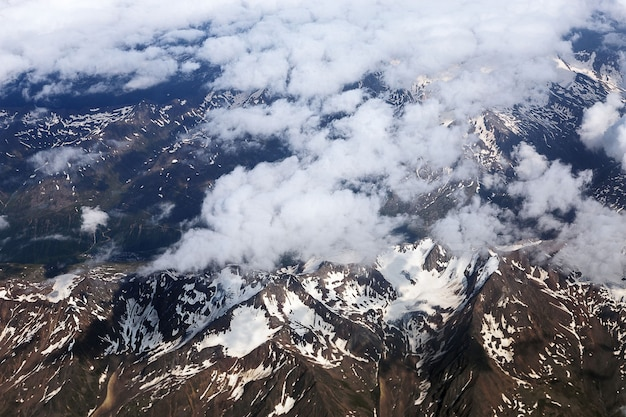 Alps and clouds from the plane. earth through the porthole. aerial view, concept of flight trip