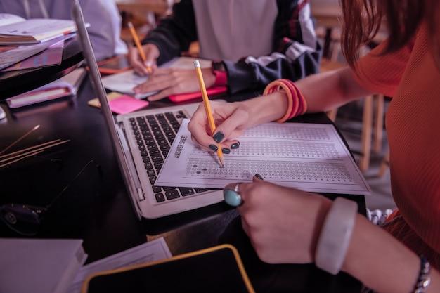 Уже сделано. внимательная молодая женщина сидит на своем рабочем месте, проверяя свою задачу