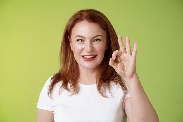 괜찮아요 쾌활한 동기 부여 결정된 빨간 머리 열정적 인 중년 여성 쇼 괜찮아 확인 제스처 확신 미소 만족스러운 제스처 승인 녹색 벽처럼 긍정적 제공