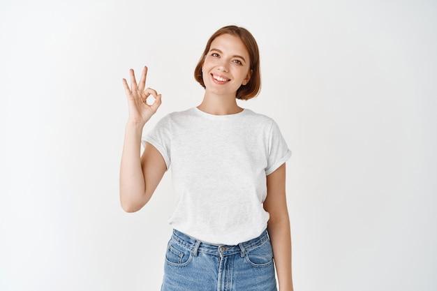Tutto a posto. sorridente giovane donna che mostra un segno ok, approva o consiglia una buona cosa, lodando l'eccellente qualità, in piedi su un muro bianco