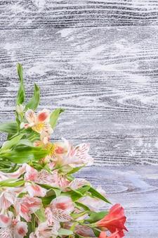 木の色の素朴な背景にアルストロメリアの花