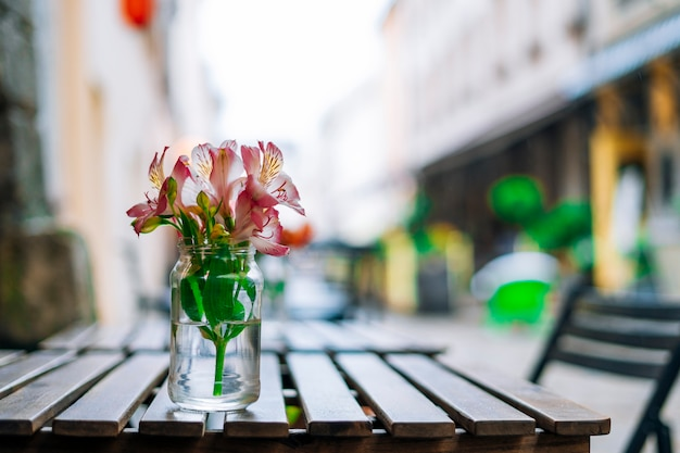 Alstroemeria flowers in vase on wooden table
