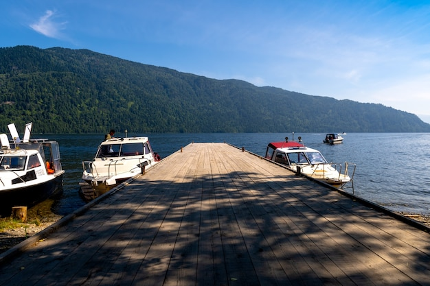 Altai, russia - july 20, 2020 - the boat is at the pier on the mountain lake teletskoye. a speedboat ride on the lake. mountain tourism. camping