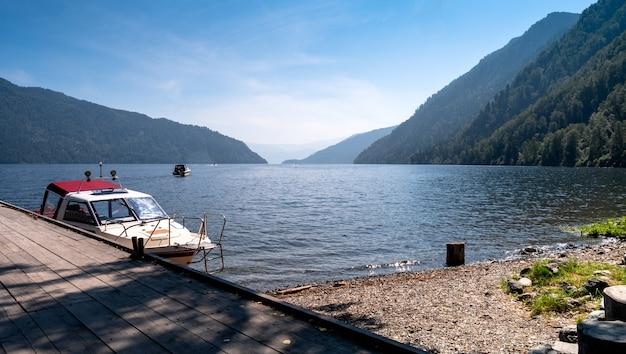 アルタイ、ロシア-2020年7月20日-ボートは山湖teletskoyeの桟橋にあります。湖でスピードボートに乗る。山の観光。キャンプ