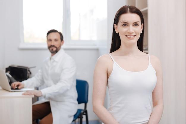自然の美しさを変える。診察室に座って美容手術を待っている立派な勇敢な元気な女性が見た目を良くしたい