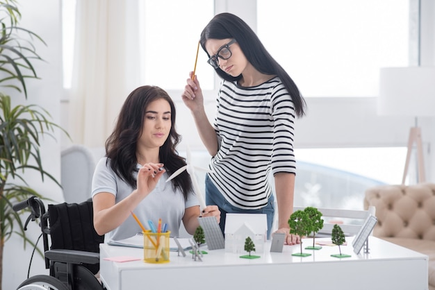 代替アプローチ。風車モデルを運ぶ魅力的な同僚の立っていると不自由な女性