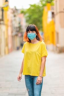 通りの真ん中に黄色のシャツとマスクを着た、オレンジの髪の白人モデル。
