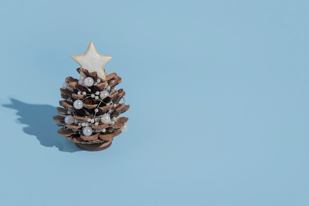 새해 카드를위한 미니멀 스타일의 복사 공간이있는 하드 그림자가있는 파란색 배경에 구슬이 달린 소나무 콘으로 만든 대체 크리스마스 트리