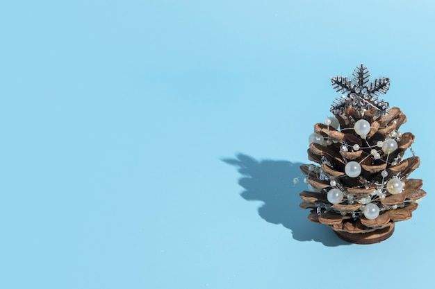 Alternative christmas tree made of pine cones with beads on a blue background with a hard shadow with copy space in a minimalist style for a new year card