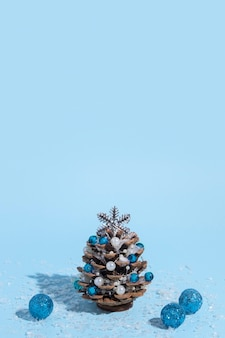 Alternative christmas tree made of pine cones with beads and snow on a blue background with a hard shadow