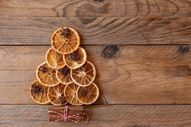 대체 크리스마스 트리입니다. 아니스 별, 계피 스틱, 나무 배경에 말린 오렌지로 만든 크리스마스 트리의 꼭대기 전망. 복사 공간, 평평한 위치. 최소한의 개념.