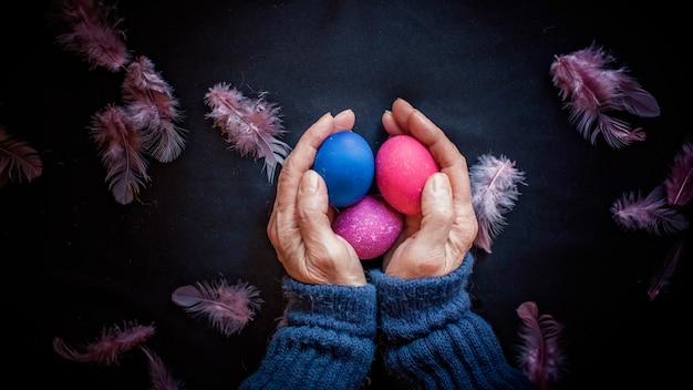 古典的な青とピンクの色の卵、黒い表面上の年配の女性の羽と手、春の季節の休日の概念と暗いスタイルの代替イースター構成