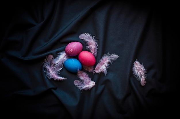 黒の上に年配の女性の卵、羽、手で暗いスタイルの代替イースター構成