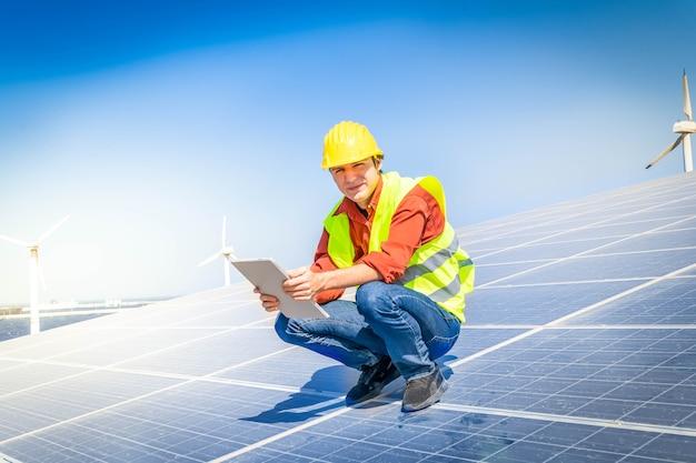 대체 에너지 개념 - 태양 전지판에 앉아 있는 엔지니어, 녹색 에너지 및 햇빛이 비치는 친환경 산업 개념