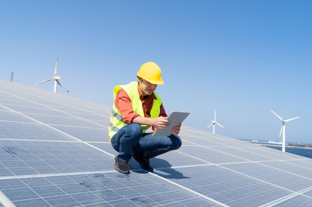 Alternative energy concept - engineer sitting on solar panels, green energy and eco friedly industry concept