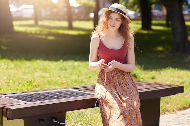 현대 도시의 대체 에너지 솔루션. 혁신적인 벤치에 앉아 공원에서 휴식을 갖는 젊은 여자