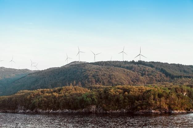 Ветряные турбины альтернативной энергии в горах на фоне моря и голубого неба