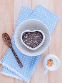 オルタナティブヘルスケアとダイエットのchia種子は、木製の背景に設定されています。