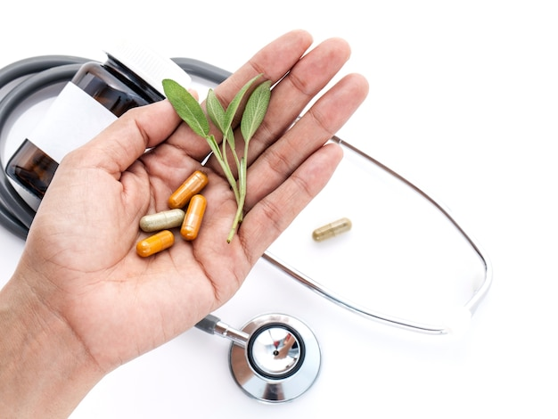 Alternative health care fresh herbal and capsule in doctor 's hand .