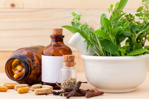 Alternative health care fresh herbs in white mortar on wooden background.