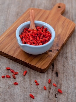 Alternative health care goji berries  on old wooden background.