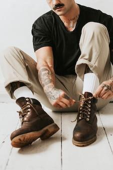 Альтернативный мужчина завязывает шнурки в ботинках на полу