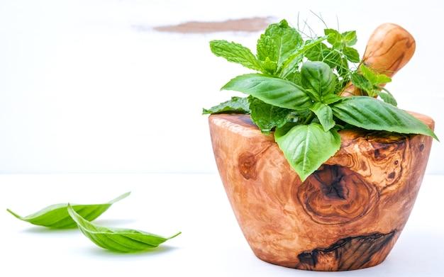 Alternative medicine fresh herbs in the wooden mortar set up on white wooden background .