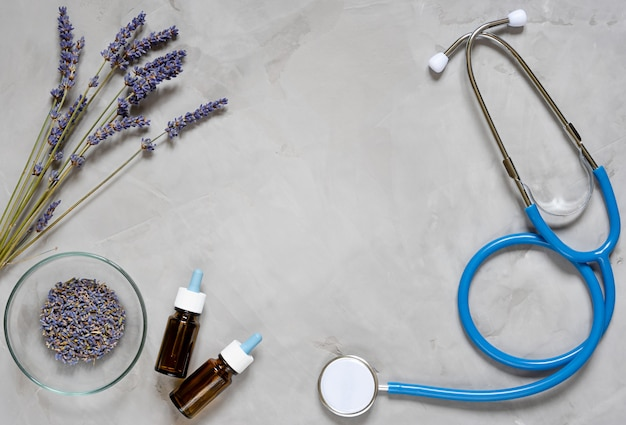 Alternative medicine herbs of lavender, oil and stethoscope on grey background