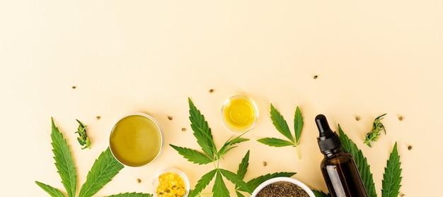 대체 의학, 천연 화장품. 도심 오일과 대마초는 오렌지 배경에 화장품 평면도를 남깁니다.