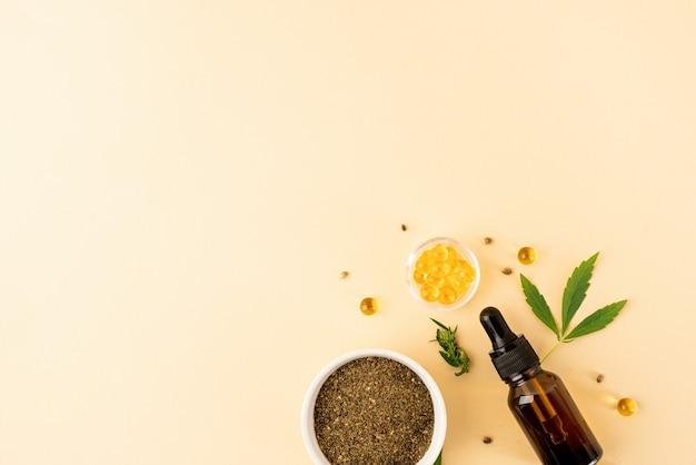 Альтернативная медицина, натуральная косметика. масло cbd и листья каннабиса косметика вид сверху на оранжевом фоне, плоская планировка