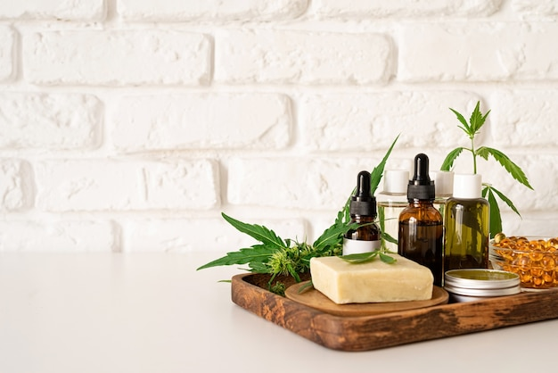 Alternative medicine, natural cosmetics. cbd oil and cannabis leaves cosmetics front view , copy space, mock up design