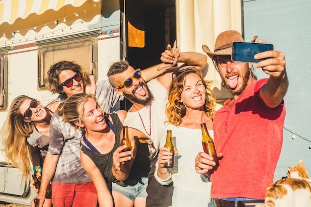 晴れた日の屋外レジャー活動で屋外で自分撮り写真を撮る友人の代替千年紀の若い白人の人々のグループは、ビールとたくさんの楽しさと笑いで一緒に祝います