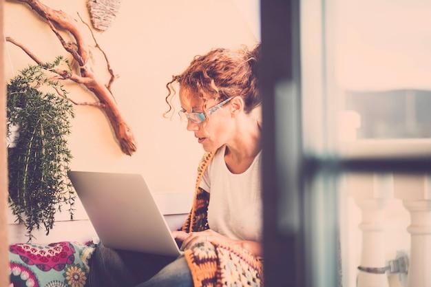 테라스에서 집에서 야외 작업을위한 대체 사무실-노트북으로 작업하는 아름다운 집중된 백인 여자-빈티지 색상 필터 스타일-프리랜서 개념