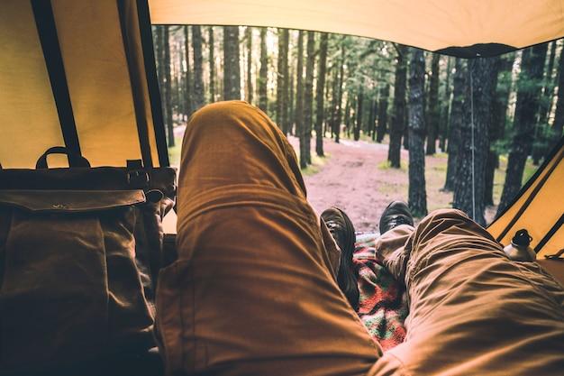 外の素晴らしい景色を望むテントの中でリラックスする人々のための代替の視点