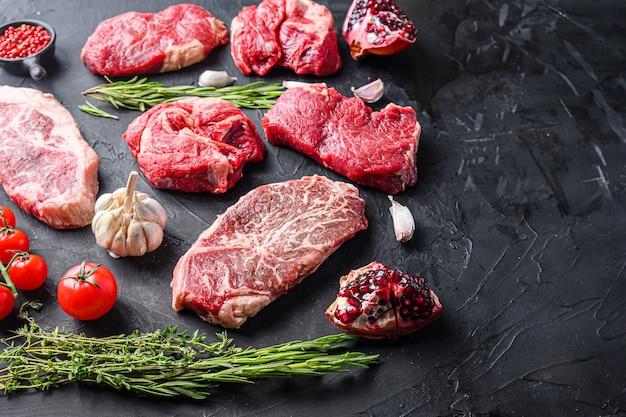 대체 생 쇠고기 스테이크는 상단 블레이드, 척 롤 및 럼프 스테이크, 허브와 석류 측면 전망, 텍스트를 위한 공간으로 잘라냅니다.