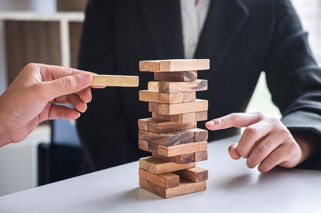 ビジネスにおける代替リスクと戦略、ビジネスチームの協力的ギャンブルの手タワーに木製ブロック階層を作成し、共同計画と開発を成功させる