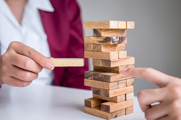Alternative risk and strategy in business, hand of business team cooperative gambling placing making wooden block hierarchy on the tower to collaborative planning and development to successful