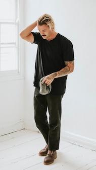 Uomo tatuato alternativo in t-shirt nera girato in studio