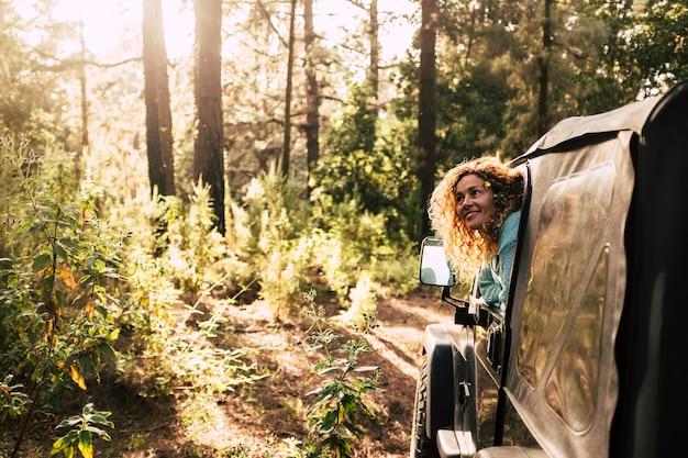 オールタナティブツーリズムの人々は、夕日の太陽の光の中で森と木を楽しむオフロード車で自然を発見します