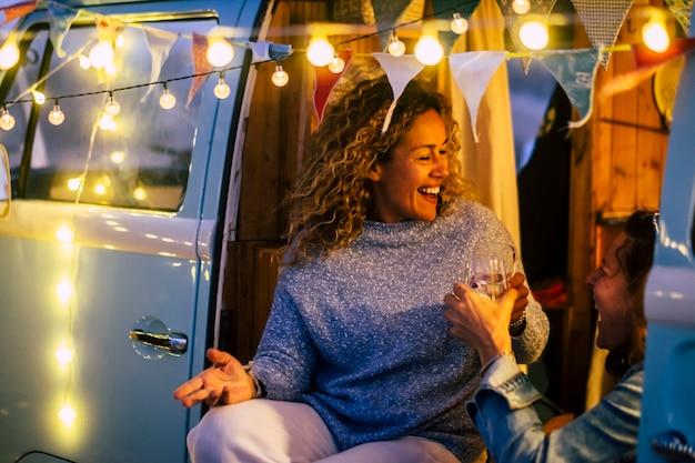 大人の陽気な幸せな女性がヴィンテージのバンキャンピングカーと屋外のパーティーライトで一緒に祝うカップルとの代替の旅行とお祝いのコンセプト