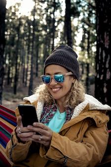 森の森の野生の自然の中で電話でメッセージを送る女性のための代替旅行休暇-美しい若い成人女性は、チャットやビデオ通話にローミングで携帯電話の技術を使用しています