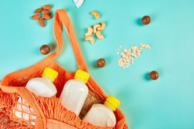 Альтернативные виды веганского молока в бутылке в сетке для покупок с орехами на синей поверхности