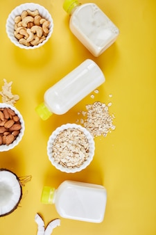 노란색 배경에 병에 담긴 비건 우유의 대체 유형, 다양한 비건 식물 기반 우유 및 재료, 비유 제품 우유