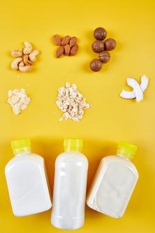 黄色の背景にボトルに入ったビーガンミルクの代替タイプ