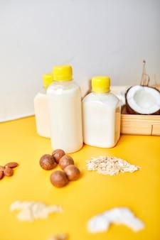 노란색 표면에 병에 담긴 대체 유형의 비건 우유, 다양한 비건 식물 기반 우유 및 성분, 비유 제품 우유, 대체 우유