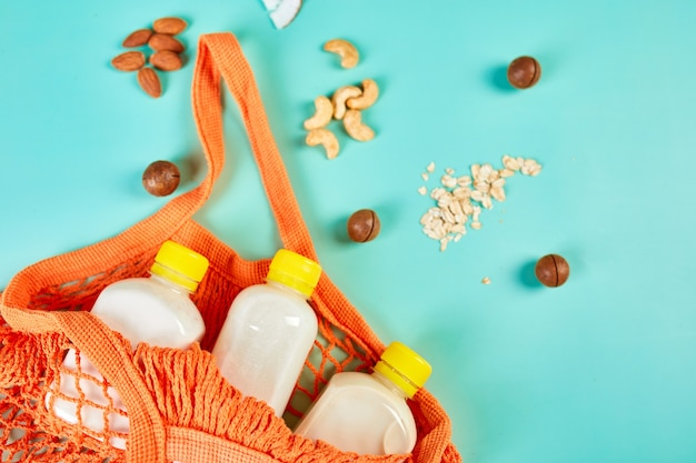 Alternative types of vegan milks in bottle in shopping mesh bag with nuts on a blue surface