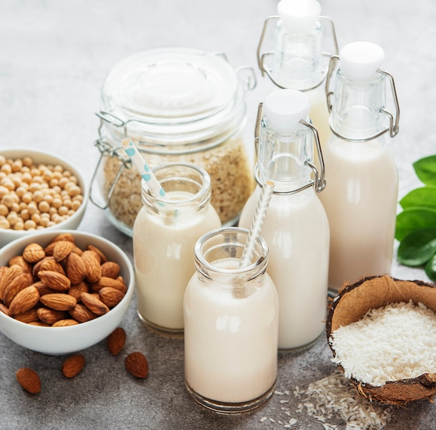 Alternative types of vegan milks in glass bottles on a  concrete background. top view