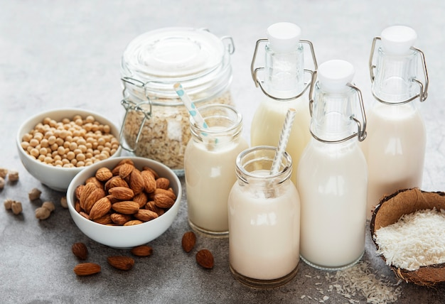Alternative types of vegan milks in glass bottles on a  concrete surface